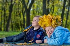 Skratta lyckliga carefree ungar i höstpark royaltyfri foto