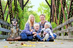 Skratta lyckligt familjsammanträde på bron i Autumn Forest arkivfoton