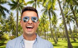 Skratta mannen i solglasögon över den tropiska stranden royaltyfri foto