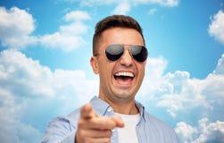 Skratta mannen i solglasögon som pekar fingret på dig royaltyfri foto