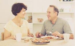 Skratta mannen och kvinnan som talar och har lunch Royaltyfri Fotografi