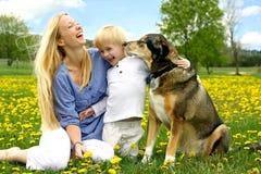 Skratta modern och barnet som spelar med hunden Royaltyfri Foto