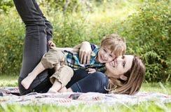 Skratta modern och barnet som utanför spelar royaltyfria bilder