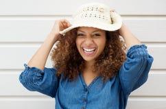 Skratta och bärande sommarhatt för gladlynt bekymmerslös kvinna arkivbild