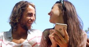 Skratta och hållande ögonen på smartphone för par stock video