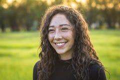 Skratta och le den härliga unga latinamerikanska tonåriga flickan utomhus arkivbilder