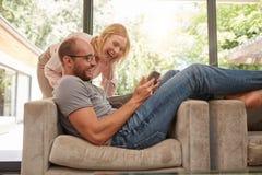 Skratta par hemma som använder den digitala minnestavlan Arkivbilder