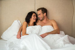 Skratta par i säng royaltyfri foto