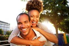Skratta par med mannen och kvinnan i omfamning arkivfoto