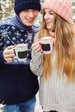 Skratta par med varma drinkar i koppar i skog Fotografering för Bildbyråer
