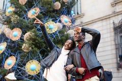 Skratta par på julsemestern som går i staden royaltyfri foto