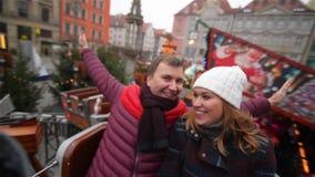 Skratta par som har gyckel i den ganska julen Vänner under vinterferie i karusellen eller karusell på stock video
