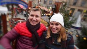 Skratta par som har gyckel i dragningen på julmarknaden, ung familj som skrattar i Xmas-mässan glatt stock video