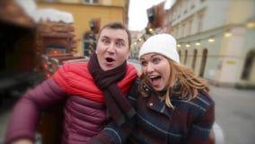 Skratta par som har gyckel i dragningen på julmarknaden, ung familj som skrattar i Xmas-mässan glatt lager videofilmer