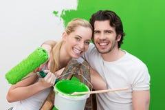 Skratta par som målar deras husgräsplan Royaltyfri Fotografi