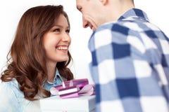 Skratta par som utbyter gåva Royaltyfria Foton