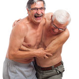 Skratta pensionärer som slåss för gyckel fotografering för bildbyråer