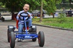 Skratta pojke i en pedal- vagn och att ha gyckel Arkivfoton