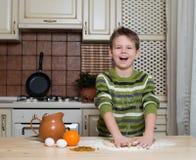Skratta pojken i köket som förbereder degen för kakor genom att använda rullning. Royaltyfri Fotografi