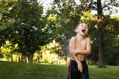 Skratta pojken som får besprutad med vatten Royaltyfri Foto