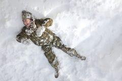 Skratta pojken som lägger i snön arkivbild