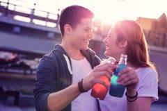 Skratta positiva unga par som dricker förnyande sodavatten från glasflaskor royaltyfri bild