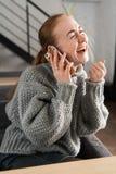 Skratta rödhåriga mannen som hemma sitter på soffan som har en konversation på telefonen royaltyfria foton