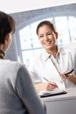 Skratta receptionist med beställare royaltyfria bilder