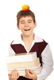 Skratta schoolboy med böcker Arkivbild