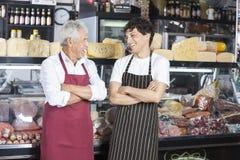 Skratta shoppar representanter med armar som korsas i ost royaltyfri foto