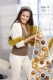 Skratta skönhet som dekorerar julträdet Royaltyfri Foto