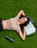 Skratta som är kvinnligt på gräsmatta som bort ser arkivfoton