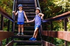 Skratta står barn i randiga t-skjortor och blåa kortslutningar rymma händer på momenten i sommaren arkivbild