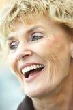 skratta ståendepensionärkvinna Arkivbild
