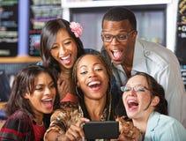 Skratta studenter som rymmer Smartphone Royaltyfri Foto
