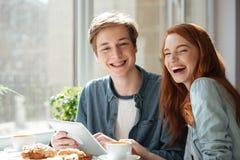Skratta studenter som sitter i kafé Arkivbild