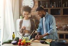 Skratta svarta par som förbereder sallad i kök royaltyfri fotografi