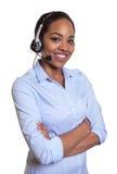 Skratta telefonoperatören med hörlurar med mikrofon och korsade armar Arkivbild