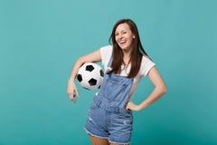 Skratta ung flickafotbollsfanjubel upp det favorit- laget för service med fotbollbollen som isoleras på den blåa turkosväggen royaltyfria foton