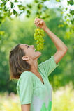 Skratta ung kvinna som äter druvor Royaltyfria Bilder