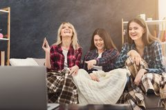 Skratta unga kvinnor som hemma håller ögonen på film royaltyfria bilder