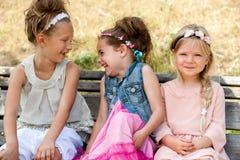 Skratta ungar som sitter på träbänk. royaltyfri fotografi