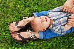 Skratta unge som lägger på mommys ben Arkivfoto