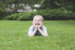 Skratta ungen på ett grönt gräs Royaltyfri Foto