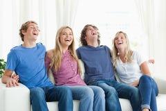 Skratta vänner sitter på soffan tillsammans Arkivbilder