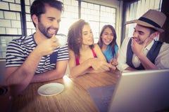 Skratta vänner som dricker kaffe och att se bärbara datorn Arkivfoto