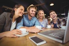 Skratta vänner som ser bärbar datorskärmen Royaltyfria Bilder