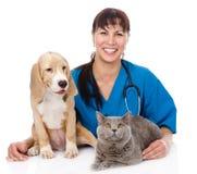Skratta veterinären som kramar katten och hunden isolerat Arkivfoto