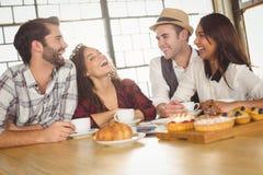 Skratta vänner som tycker om kaffe och fester Arkivbild