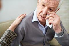 Skriande äldre man som har sjuksköterskahjälp arkivfoton